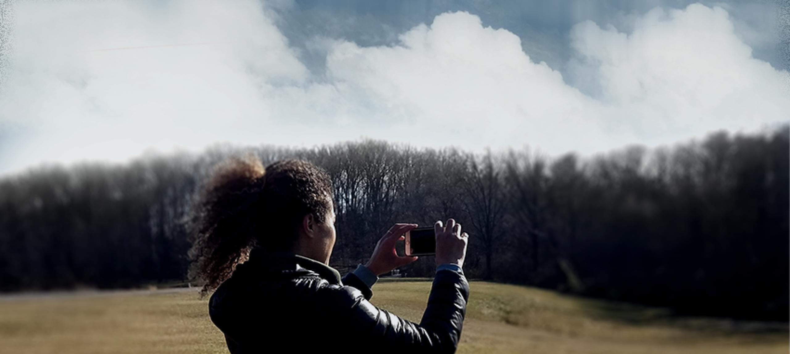 Photo of woman standing in a field taking a photograph