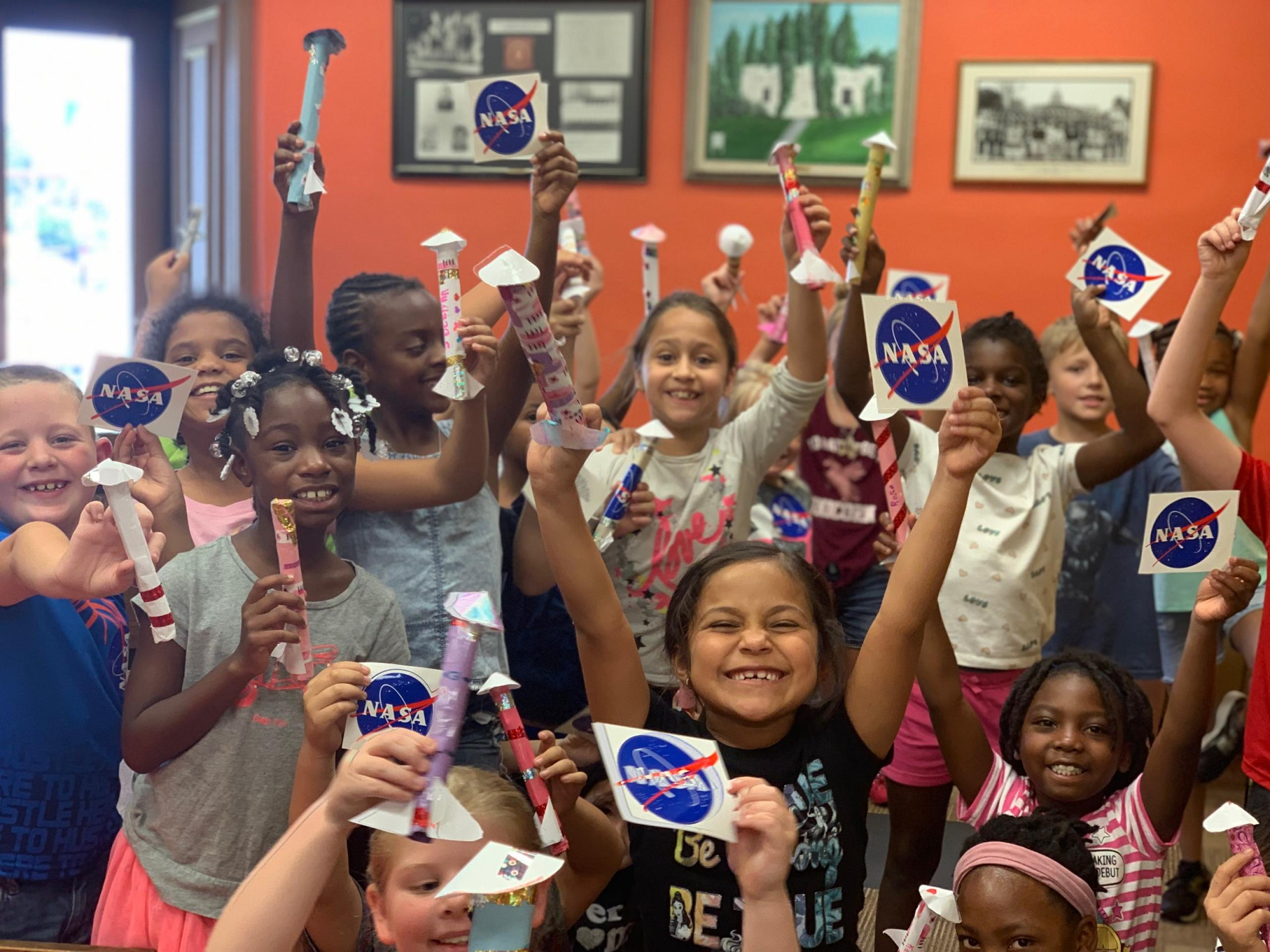 Children showing off their paper rockets and NASA stickers.