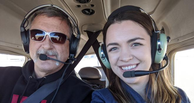 Kaley and her father, Lee, wearing headsets in a small airplane cockpit.