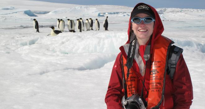 Photo of scientist Heather Lynch in front of a colony of penguins