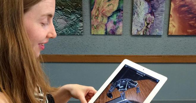 Elizabeth Landau holding an iPad with an augmented reality app.