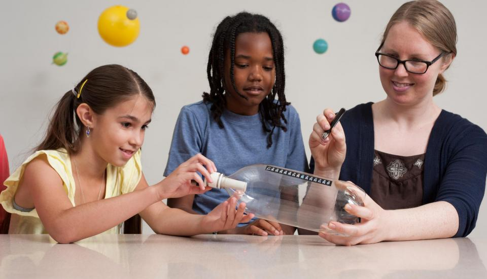 Photo of teacher and students doing a science experiment.