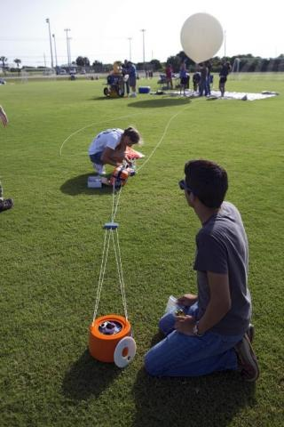 Two students in a field preparing a white balloon for launch