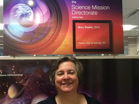"Mary F. Sladek in front of a poster board with her name and ""Science Mission Directorate""."