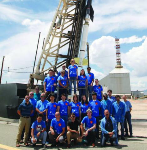 Photo of the 25 FOXSI team members wearing blue shirts and standing in front of the sounding rocket.
