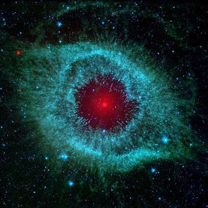 Cosmic starlet known as the Helix Nebula that resembles a teal eye with a red pupil.