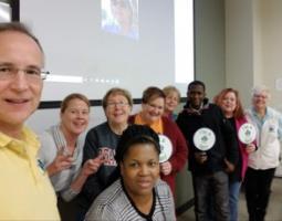 Kevin Czajkowski & eight GLOBE Mission EARTH teachers posing in front of a projector screen.