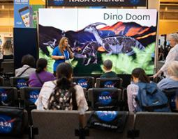 "A woman stands in front of a wall of screens reading ""Dino Doom""."