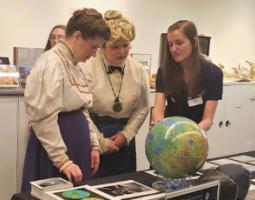 Annie Jump Cannon and Henrietta Leavitt cosplayers looking at a lunar globe.