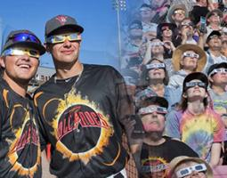 Salem Keizer Volcanoes fans and players wearing eclipse glasses