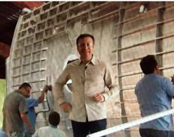 Meteorologist Guillermo Quiroz standing in front of a wooden wall that several men are constructing