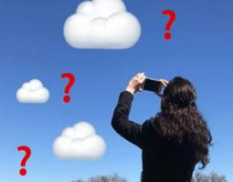 A woman holds a phone up to animated clouds.