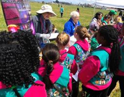 Girl Scouts in pink sweatshirts and teal vests at an activity booth