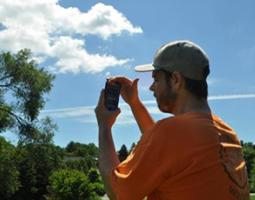 A man uses a smartphone to do cloud observations