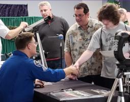Astronaut Doug Wheelock shakes a young man's hand.