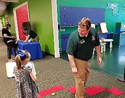 A little girl holds a dry-erase board next to a man in a green polo.