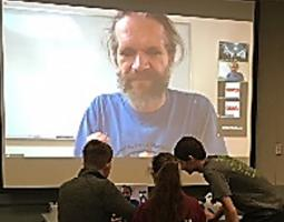 Three students in front of a projector screen and laptop. On the displays are a bearded man via webcam.