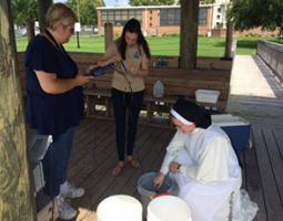 Three female teachers gather around buckets on a wooden deck