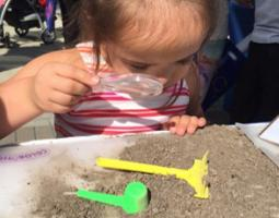 A little girl looks at soil through a magnifying glass