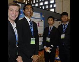 Group of male students assembled in front of scientific poster board