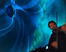 Man playing violin in front of projected earth image
