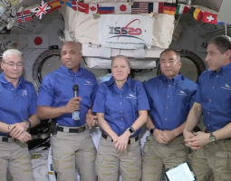 Still screen of video of 5 astronauts on the International Space Station