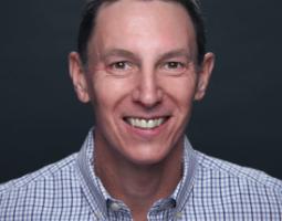 Portrait photo of a smiling man wearing a blue plaid shirt