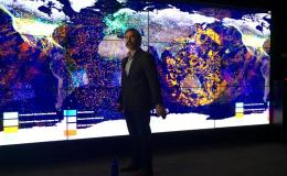 Photo of John Bolten standing in front of a large monitor displaying Earth science data.