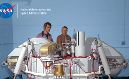 Photo of two men standing behind the Viking Lander spacecraft