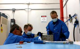 Two men and one woman in blue lab jackets work on HaloSat hardware on a table.