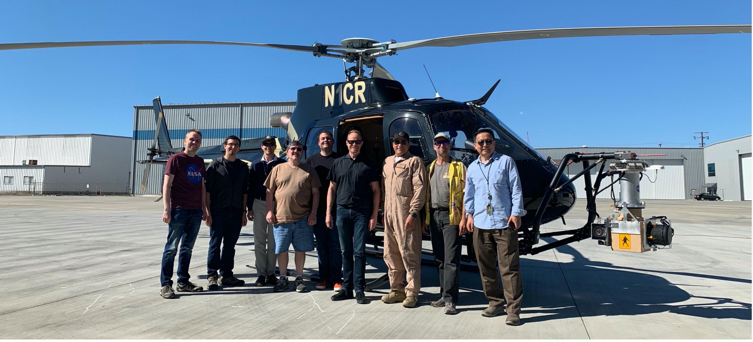Photo of men standing in front of a helicopter