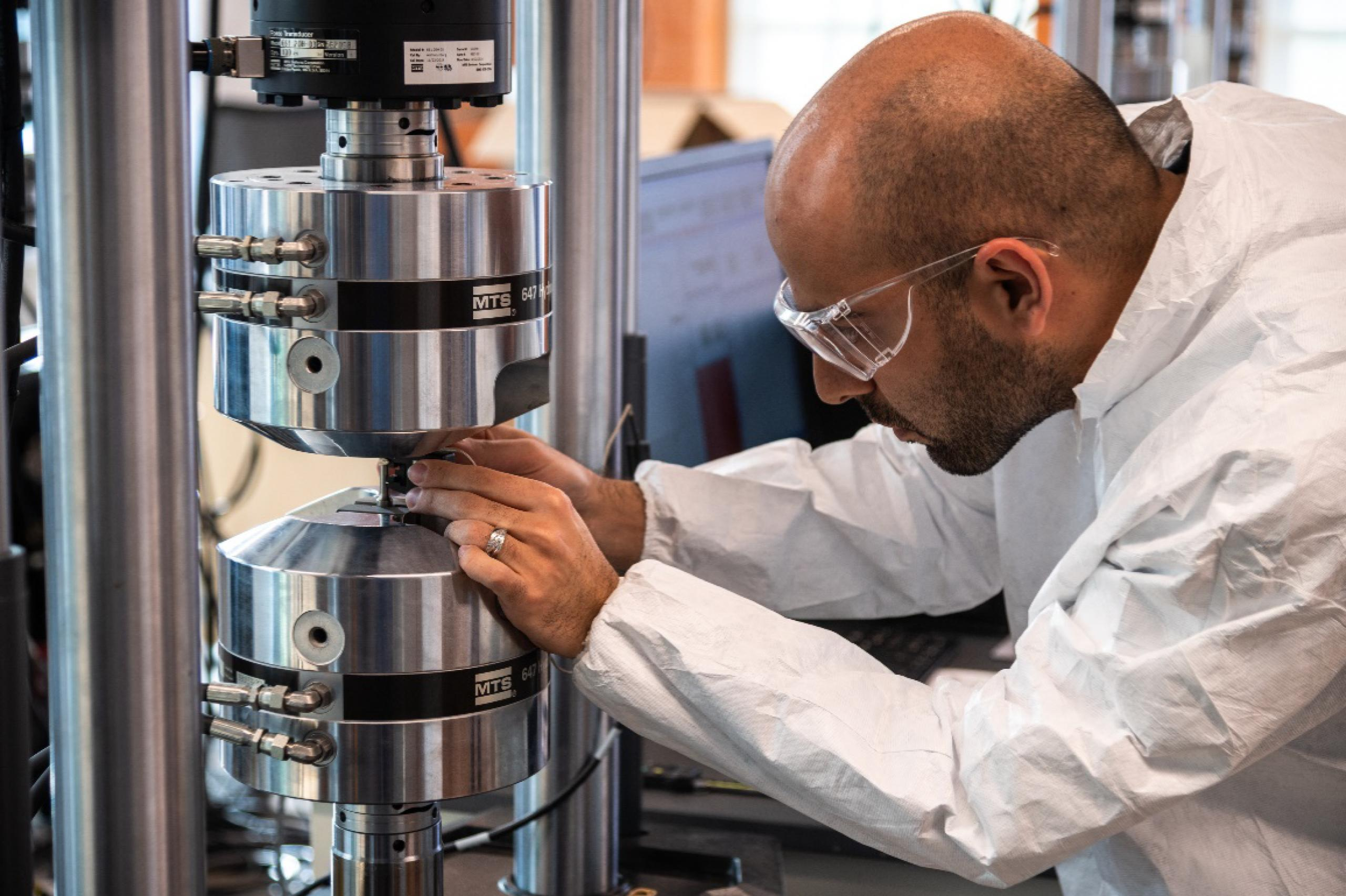 Man attired in lab clothing and classes working with his hands on a metal cylinder.