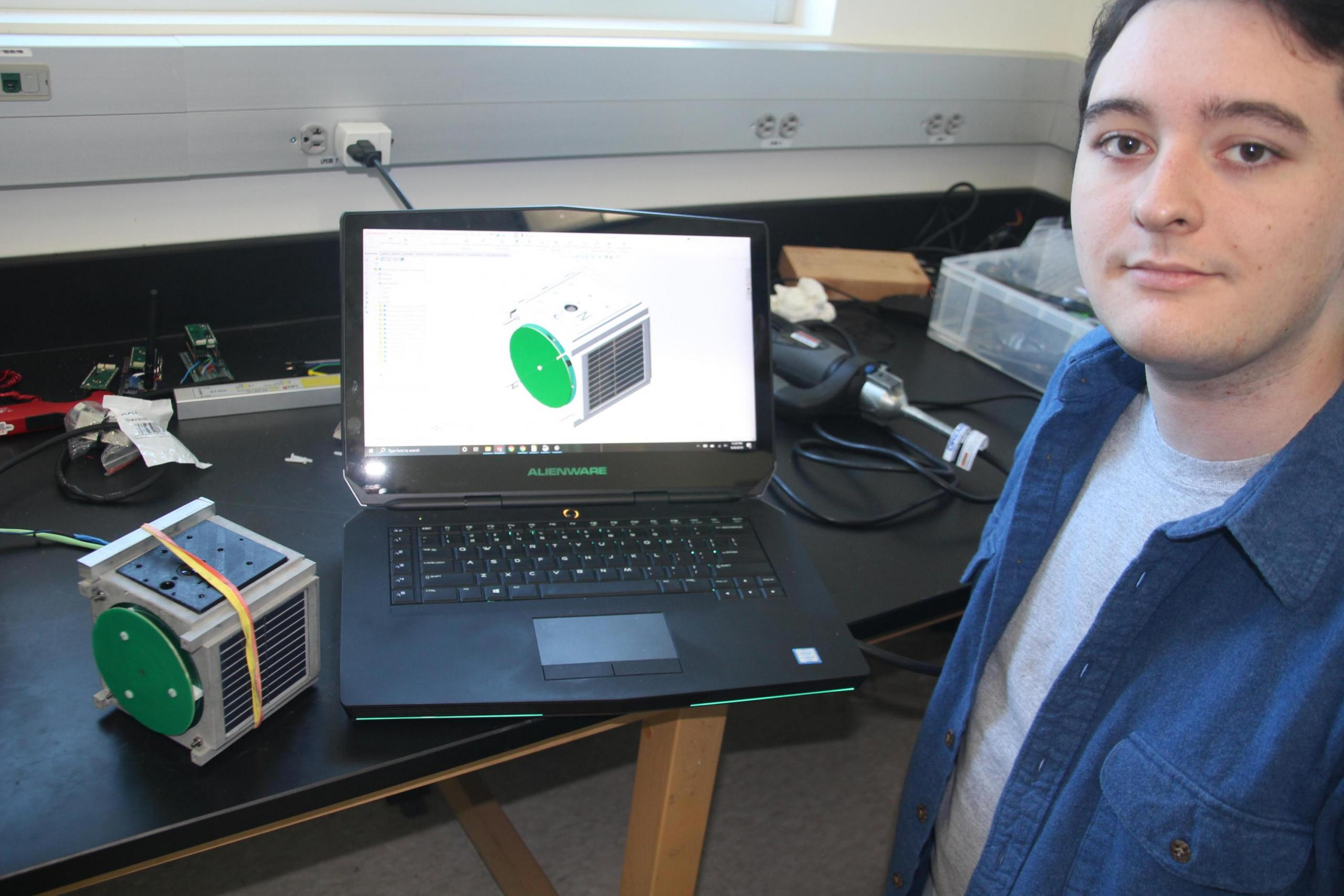 Alex Vasquez next to a computer screen on which the CAD model of SSU's EdgeCube satellite is displayed. Also shown is a model of EdgeCube.