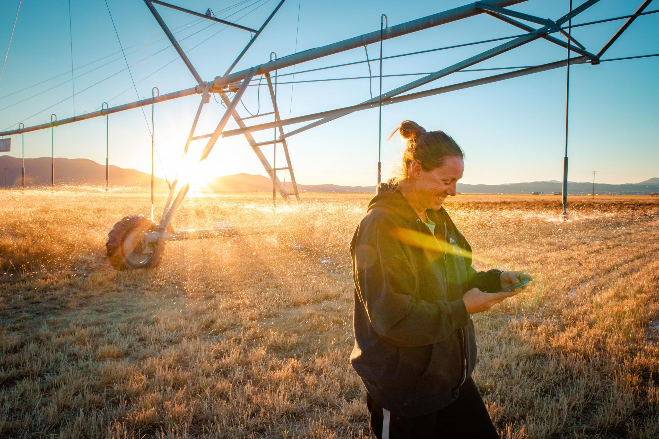 Woman standing in a crop field with irrigation equipment.