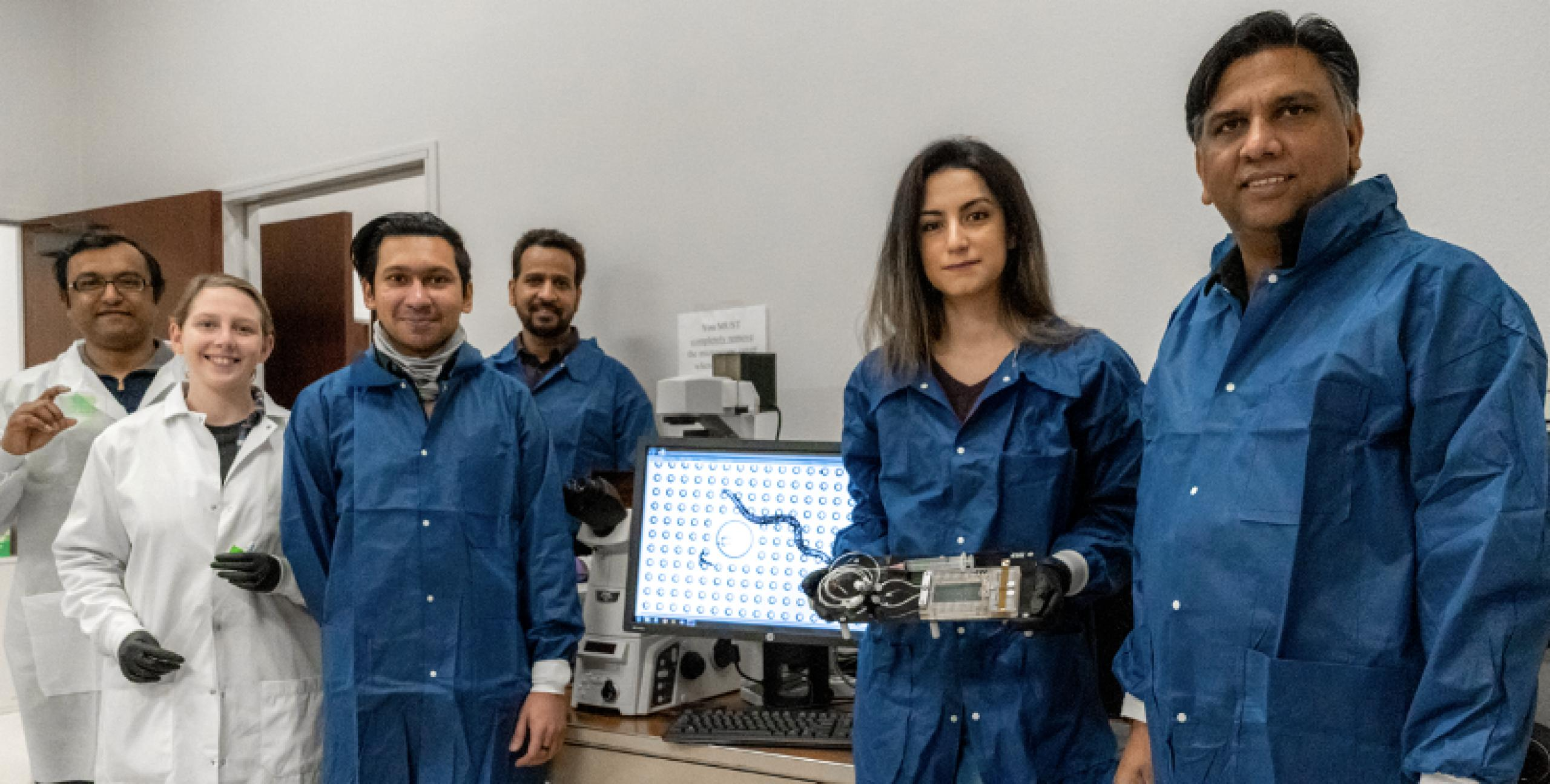 Photo of 6 research scientists wearing lab gear and holding science experiments and equipment.