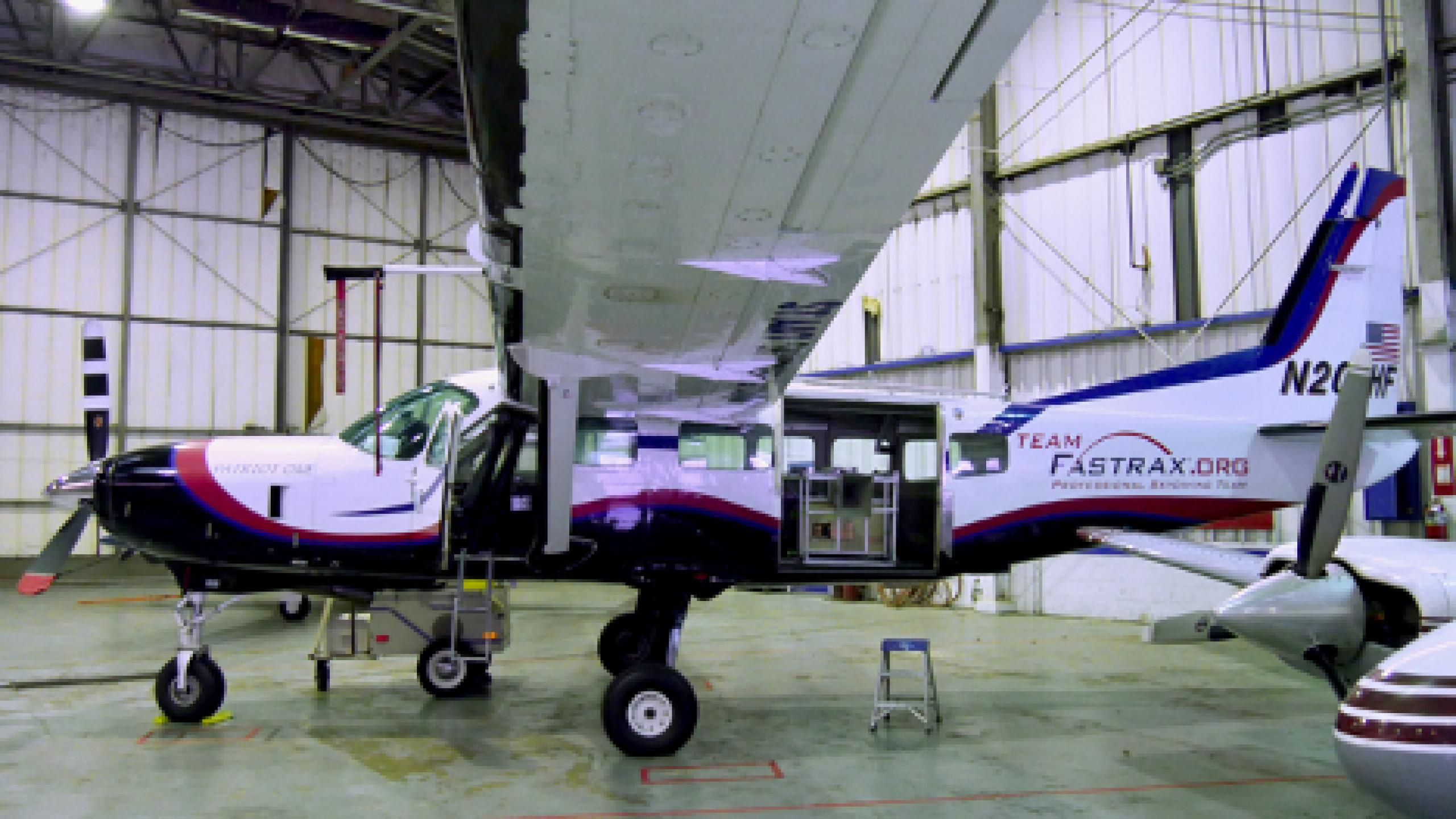 Photo of small airplane being loaded with the CubeSat