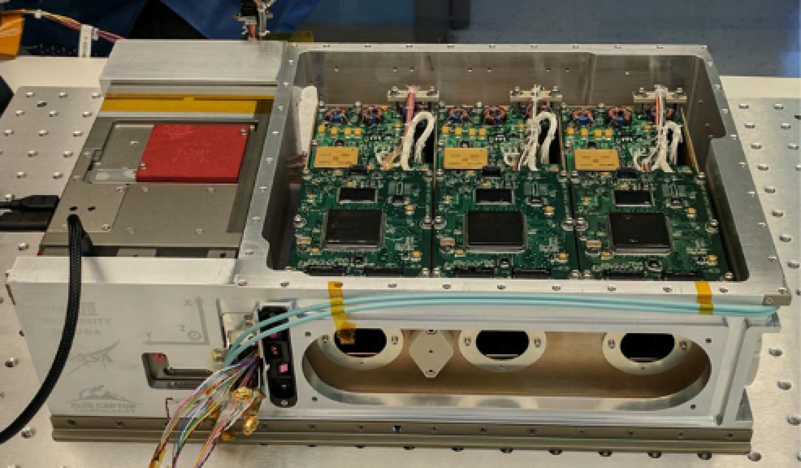 Photo of HaloSat hardware, a tan box on the left and electronic circuit boards and an Xray lens