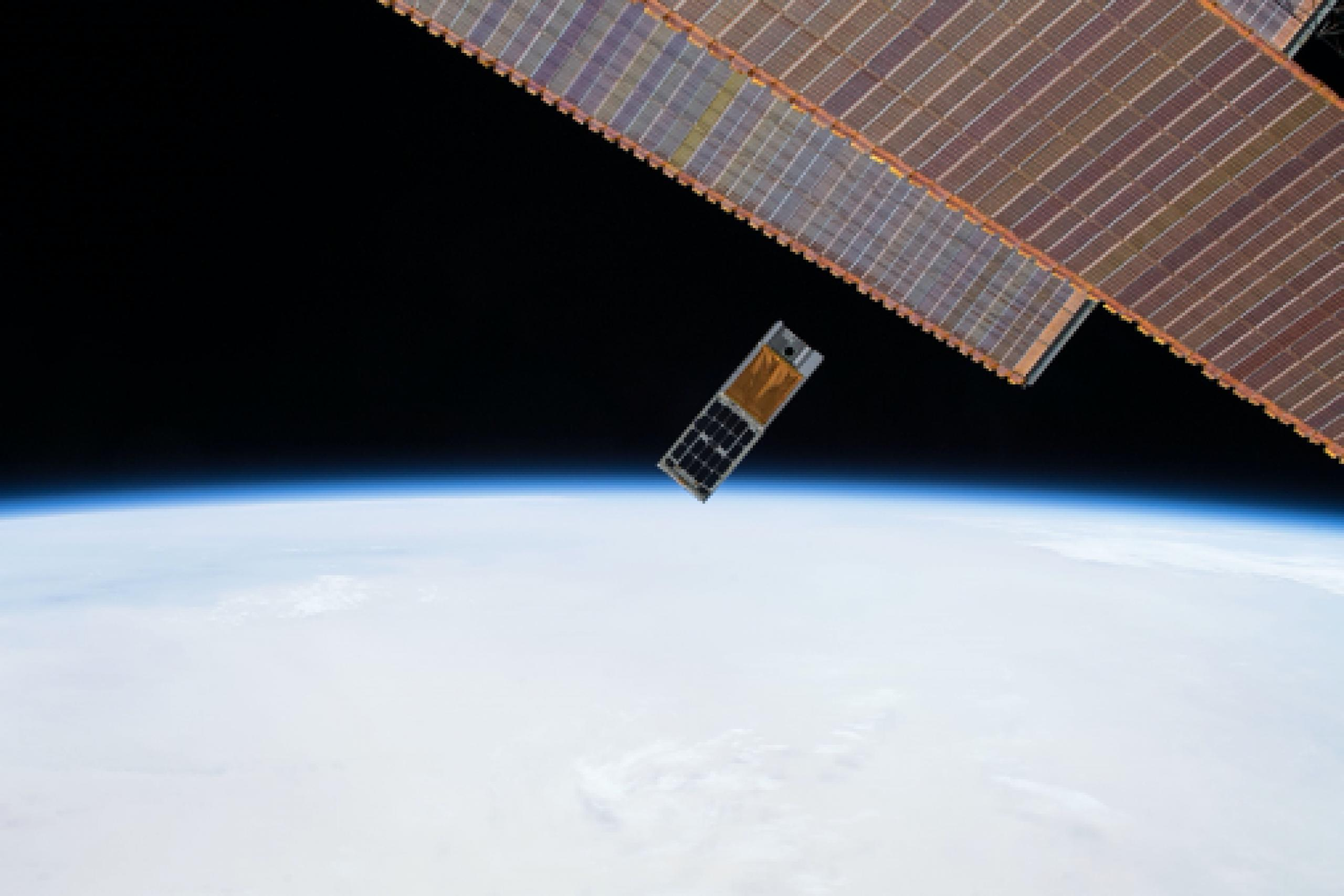 Photo of the HaloSat hardware box after being deployed from the ISS; the ISS solar arrays are to the right with Earth in the background.