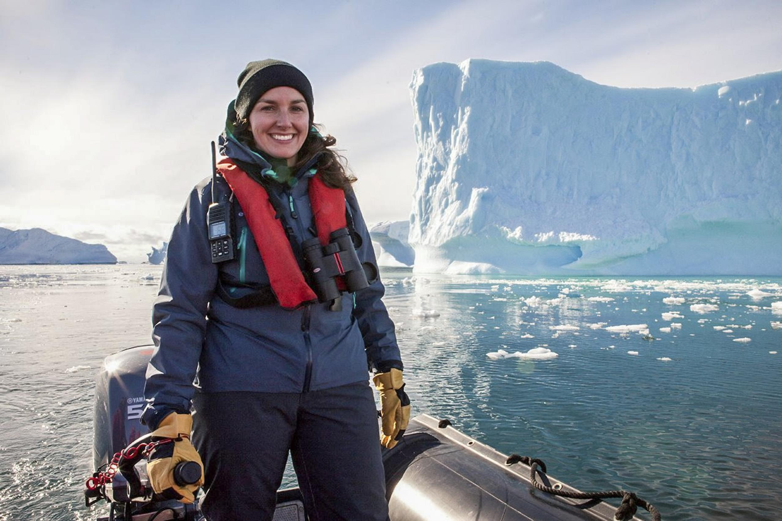 Photograph of woman dressed in winter gear standing in a boat with a large glacier in the distance behind her
