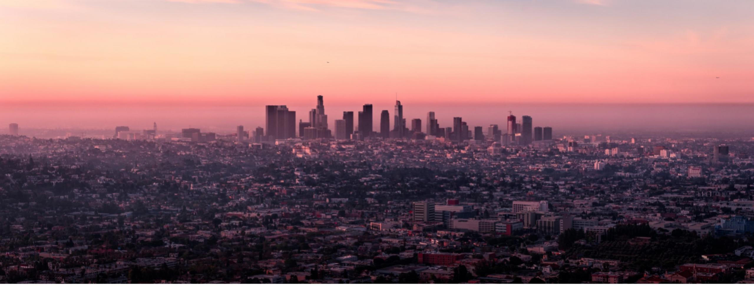 Photo of a hazy sunrise behind the LA landscape.