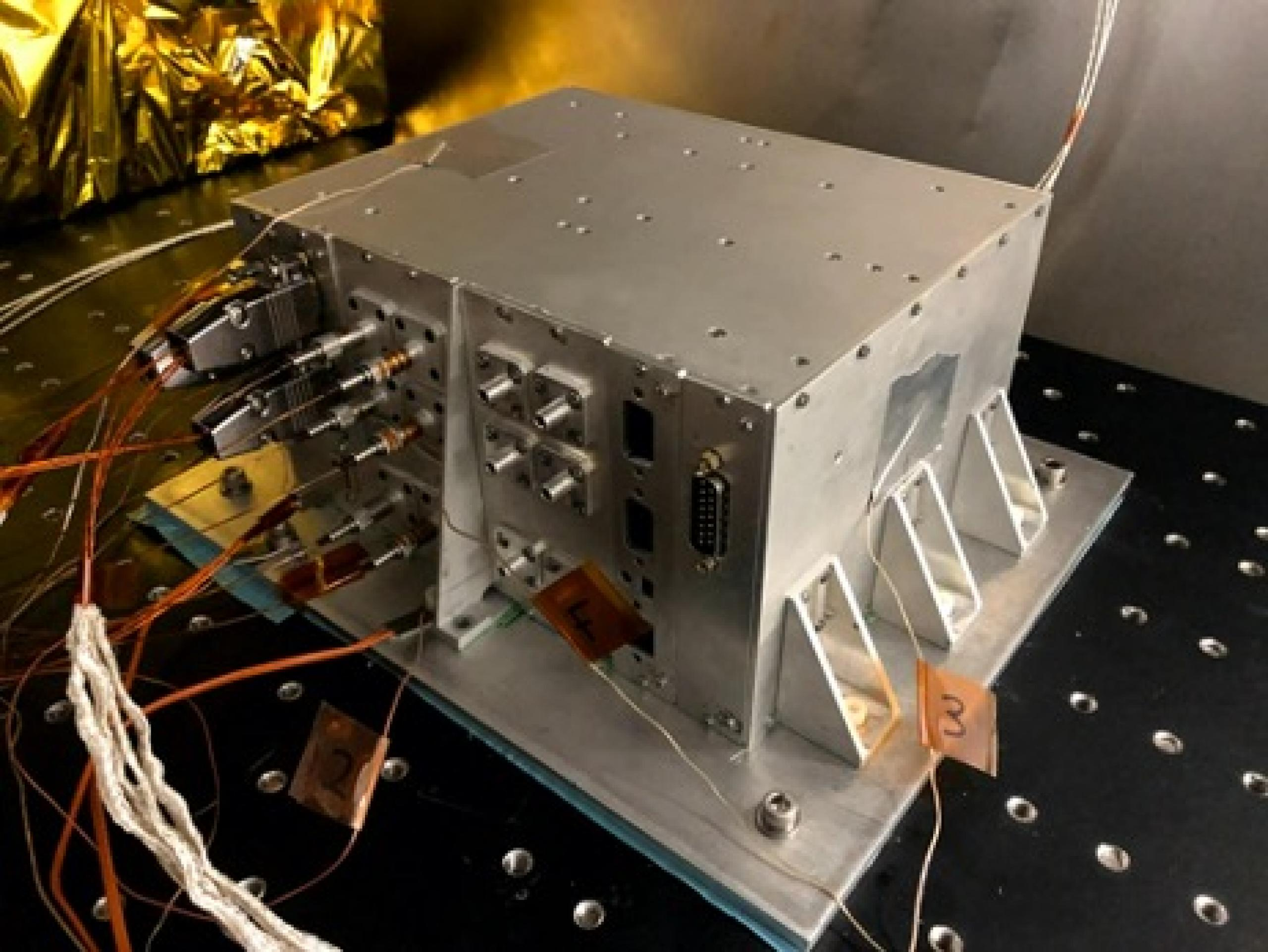 Photograph of silver colored metal hardware box with several colored wires plugged into it