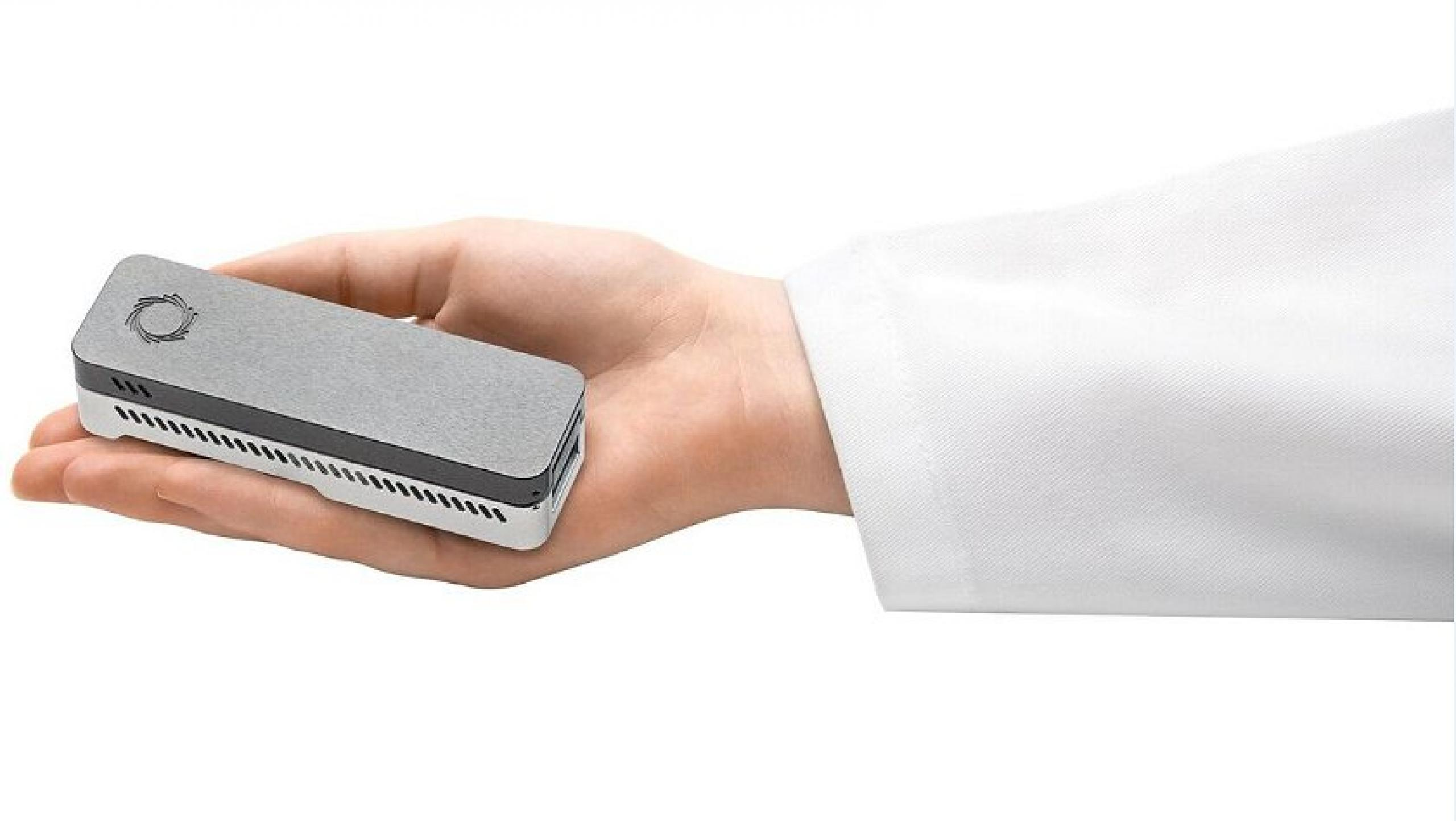 Rectangular gray equipment resting in the palm of a hand.