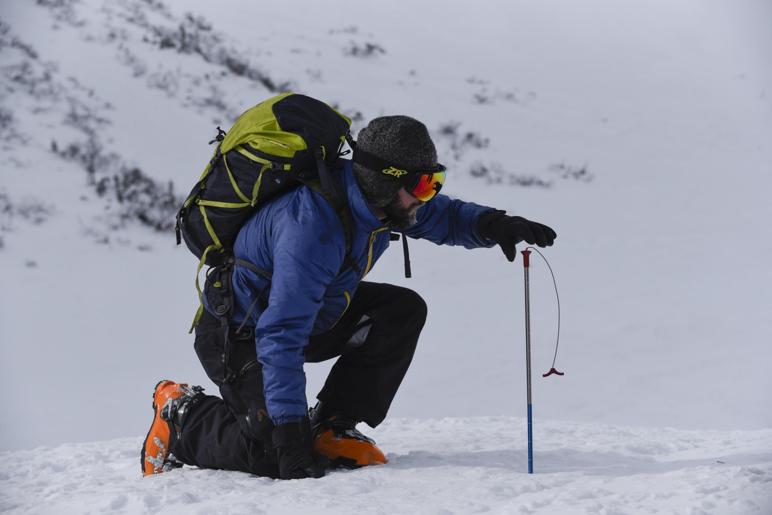 Ryan Crumley measures snow depth in the White Mountains of New Hampshire.