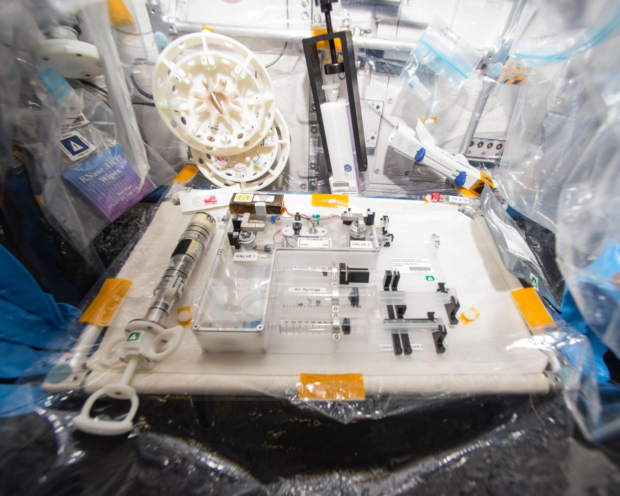Lab with test equipment comprised of syringes, plastic containers, and other apparatuses.