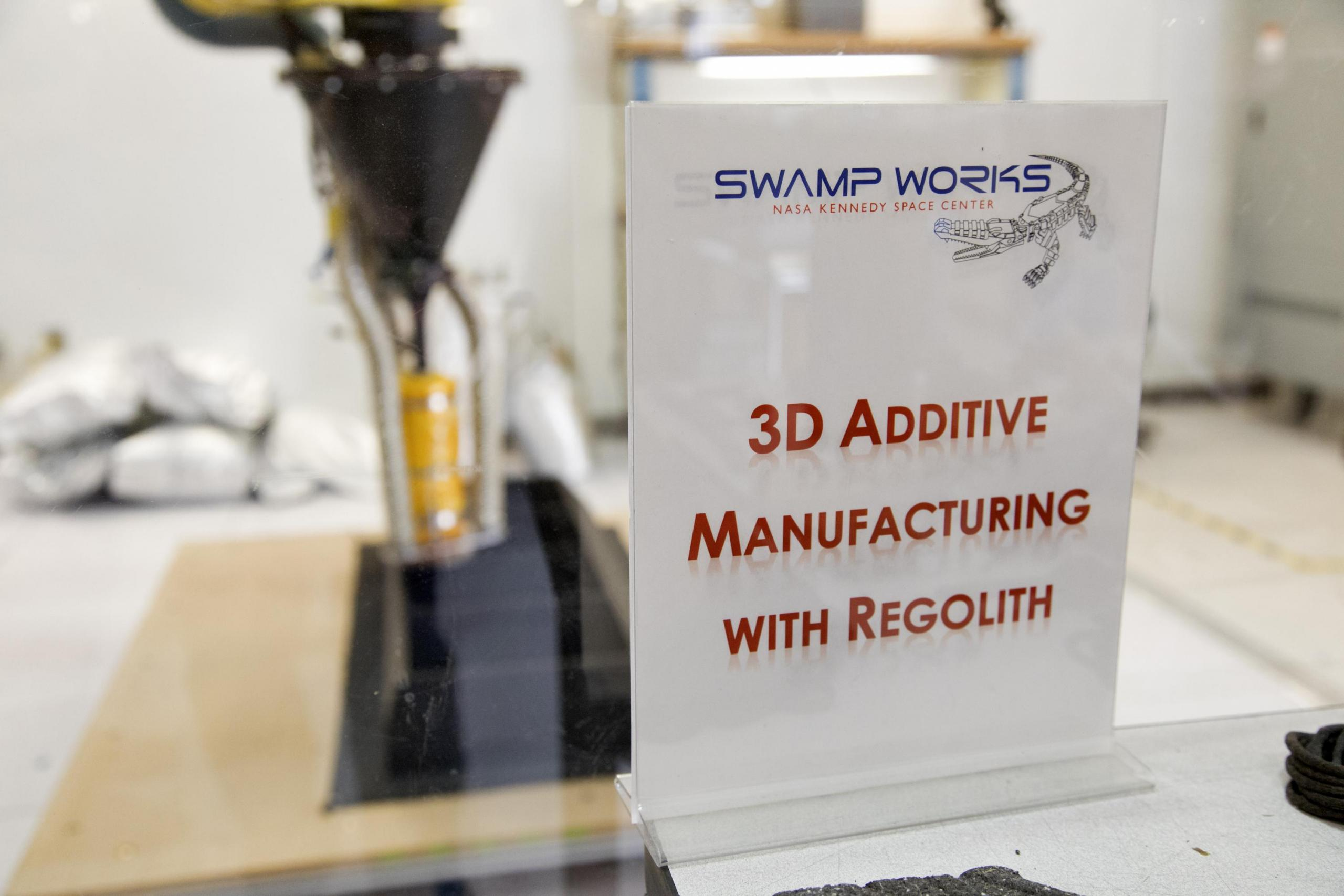 The 3-D printer used to make things out of lunar dust (regolith) at the Kennedy Space Center.  Additive manufacturing is another name for 3-D printing.