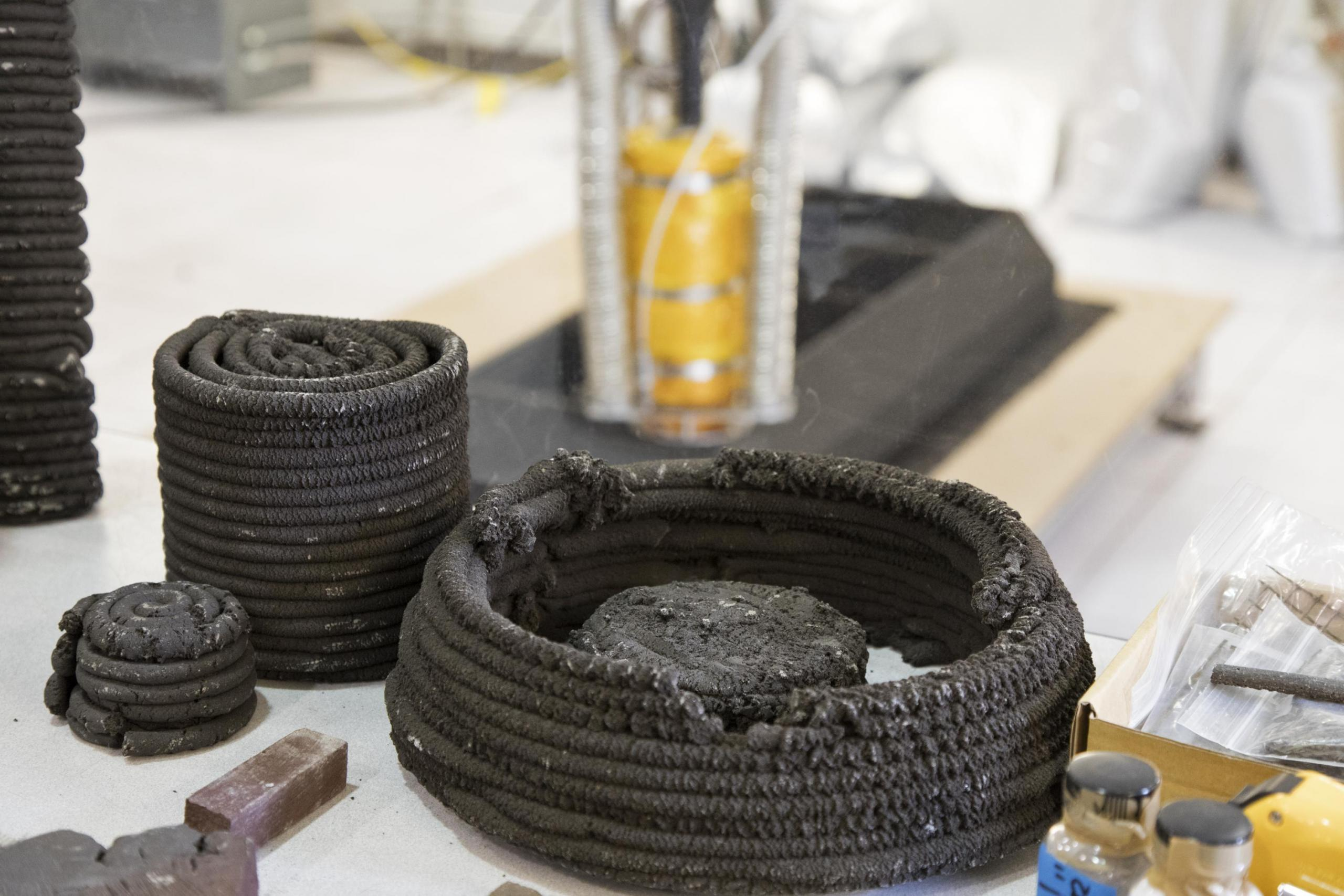 Coils of dark-colored material that were made by a 3-D printer out of simulated lunar dust.