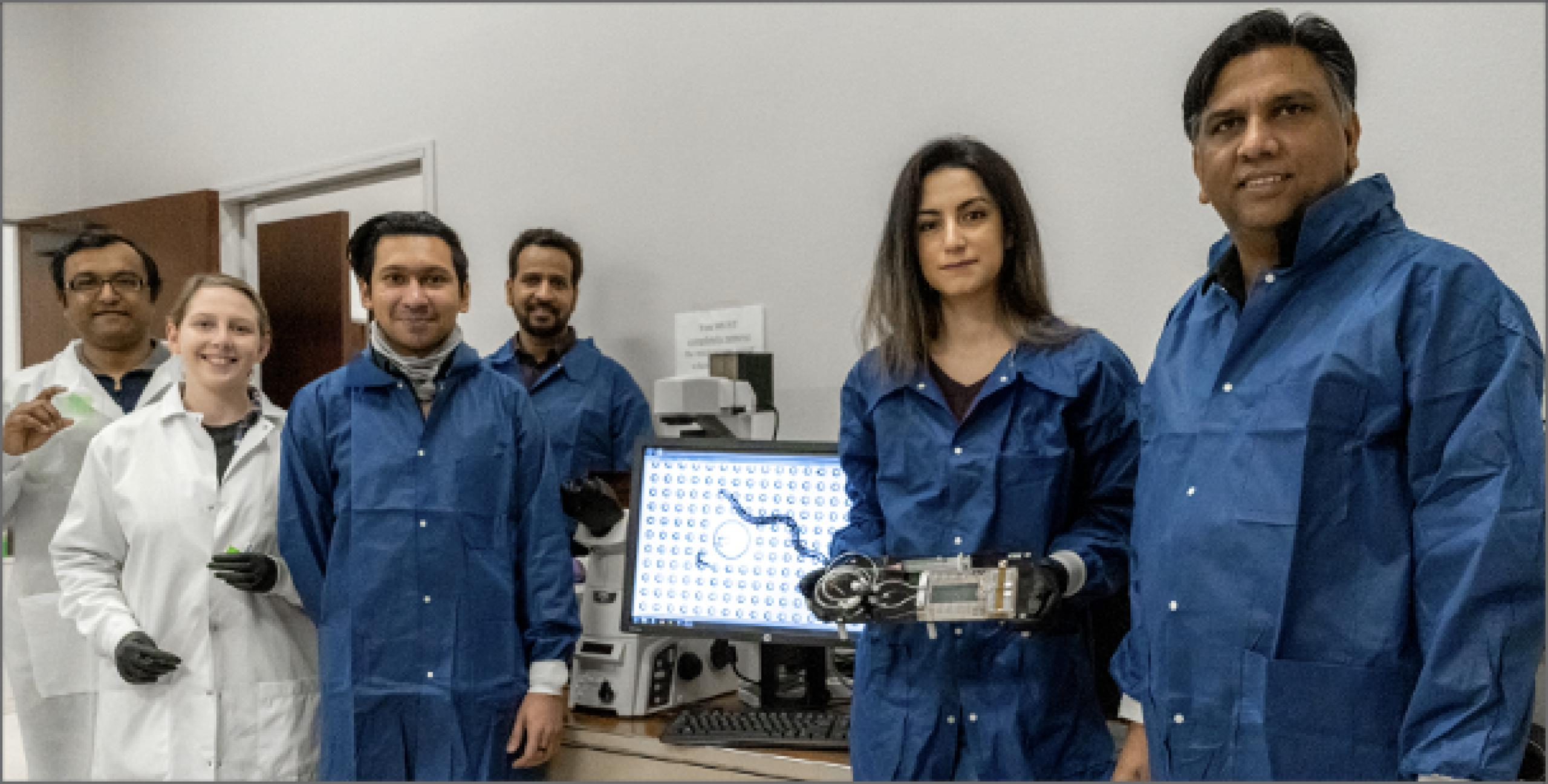 Group photo of 6 research scientists in blue and white lab gear holding lab equipment.