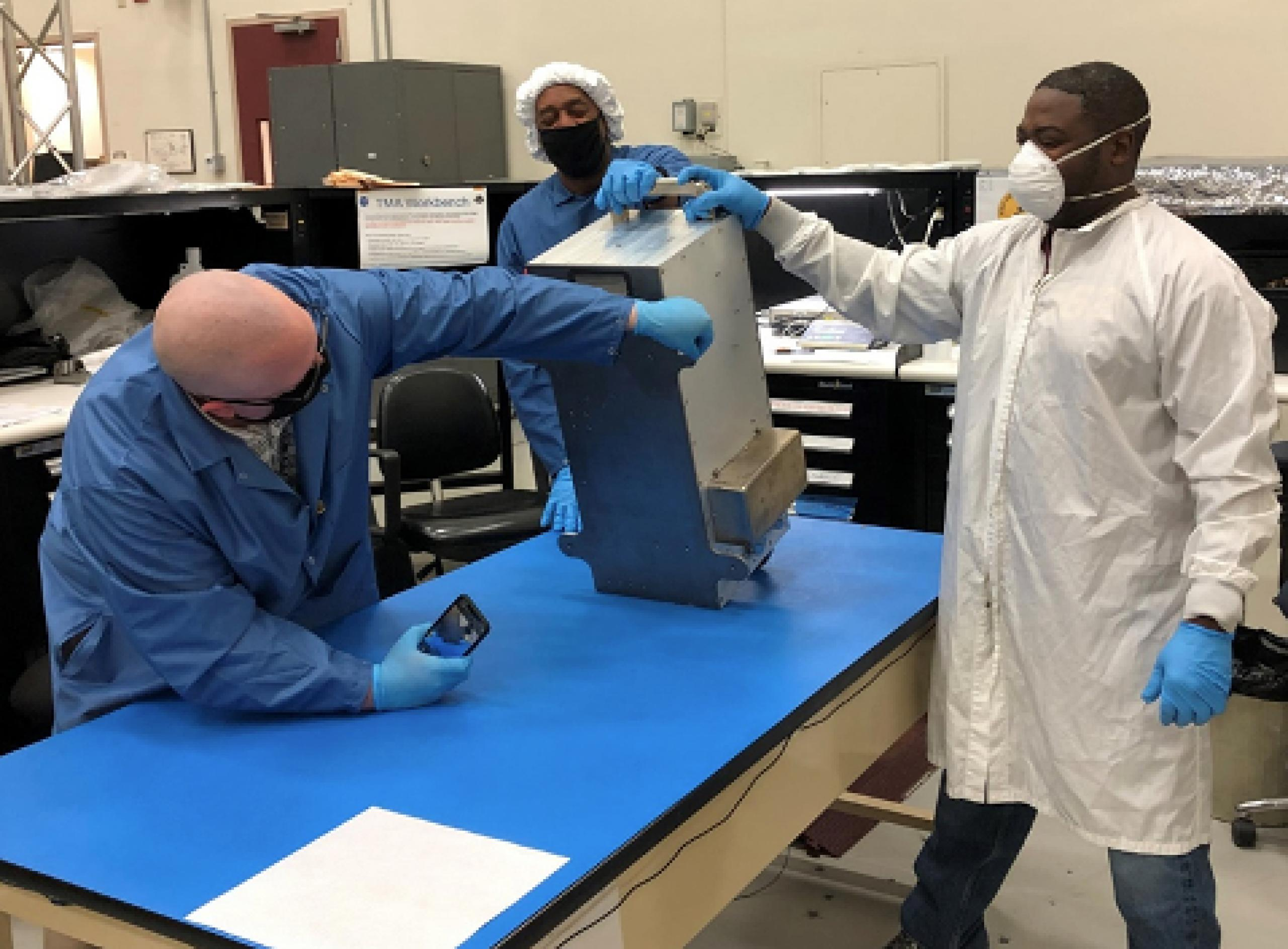 A metal mechanical box sits at an angle on a table, as three individuals - wearing gloves, lab coats and face masks - examine the box by touching the surface and photographing the box.