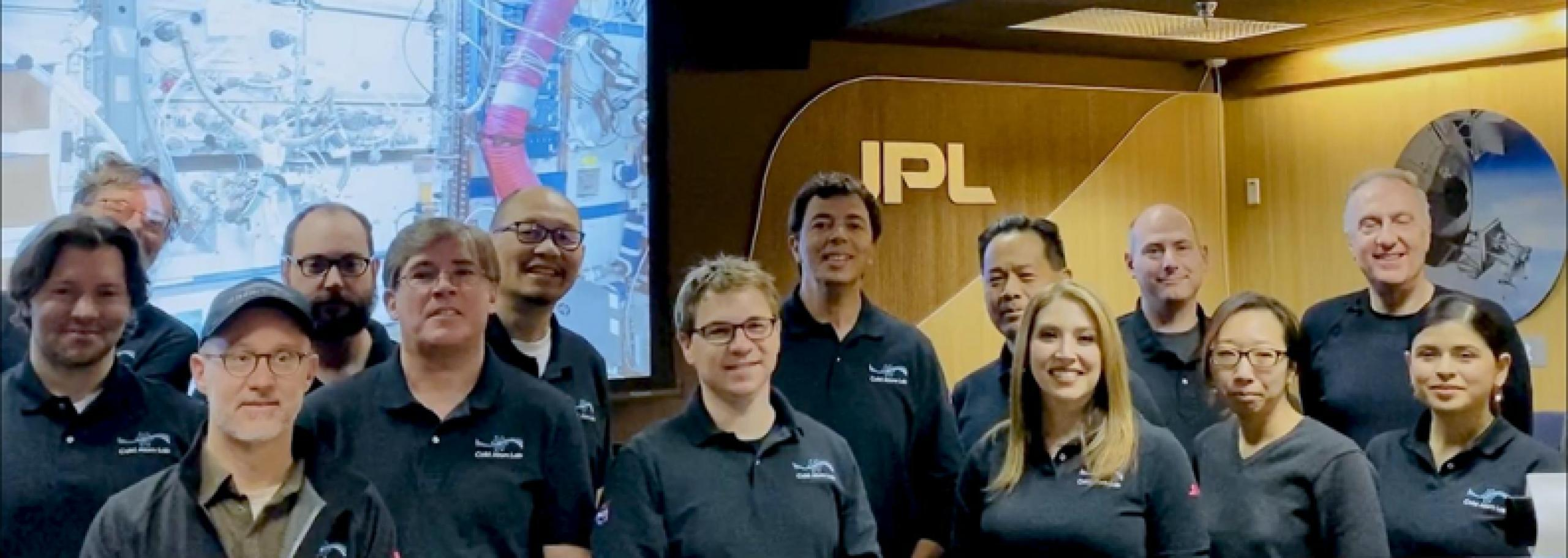 Photo of group of researchers and scientists standing in front of a monitor and JPL sign