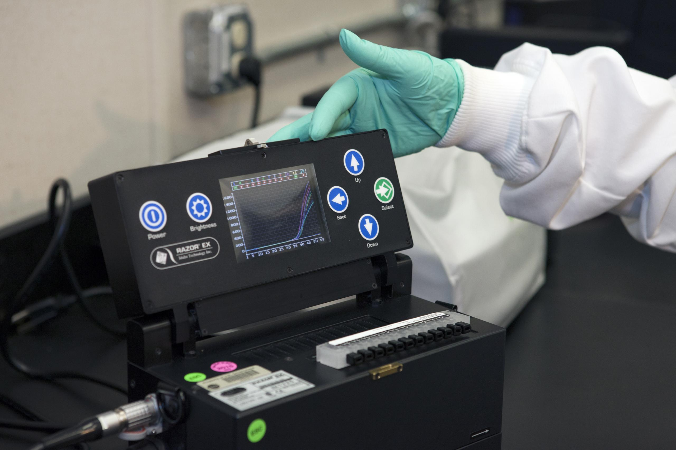 Scientist's hand pointing to display on black test equipment.